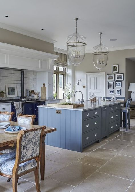 Gorgeous French blue kitchen island with navy blue lower cabinets and beige stone floors.
