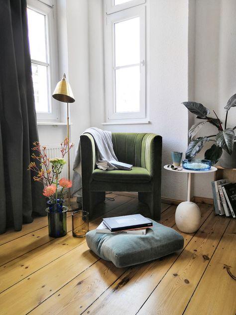 skandinavisches design mit gruenem samtsofa marmortisch leselampe in berliner altbau