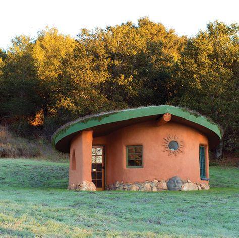 A tiny cob cottage sits in dusky light.