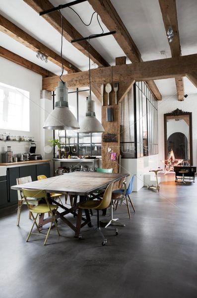 Une salle à manger industrielle charpentée de bois brut