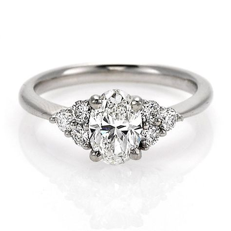 An oval cut diamond solitaire of 1.07ct G colour VS1 clarity set in a platinum mount with 3 round brilliant cut diamonds on each side of 0.37ct total weight. GIA Certificate.