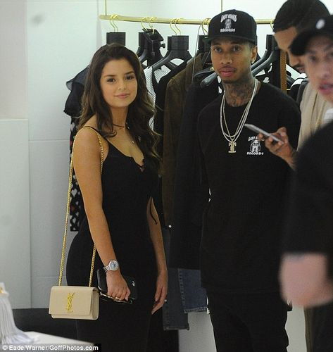 Dressed to the nines: As they browsed the YSL shop, Demi showed off a tan, YSL bag with a ...