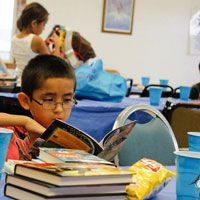 Lower Brule welcomes new library. Article contributed by Mary Richey, Lower Brule Community College library director. Photo of Child reading at Lower Brule Community College Library, #SDSLCornerstone