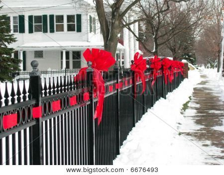 Outdoor Christmas Ribbon.Red Ribbon Bows On The Iron Fence Along A Small Town Street