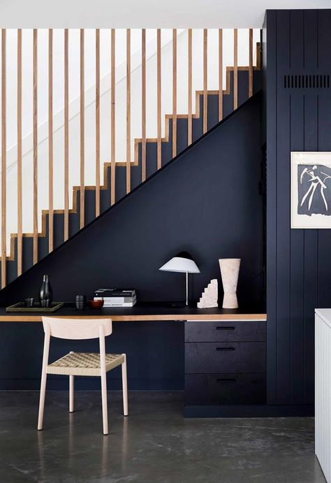 The blackbutt timber staircase with battens is paired with a clever in-built study nook underneath. The study area is painted black, creating visual integration. The concrete polished floor adds a soft contrast.