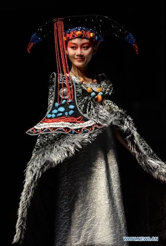 A model presents a traditional ethnic fashion creation during the 2013 China (Qingdao) International Fashion Week in Qingdao, a coastal city...