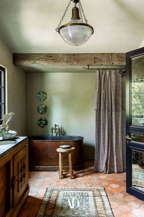 The main bath is furnished with a 19th-century copper tub with Watermark fixtures, a Charles Dudouyt vanity, an English Holophane light from Obsolete, curtain fabric by Heather Taylor Home, reclaimed terra-cotta floor tiles from Chateau Domingue, and a door that once graced Jacqueline Onassis's New York City apartment. #green #greenpaint #greenwalls #greendecor #coloroftheyear #bathroom #tub #bath #vanity #shower #lighting #rug #selfcare #routine #beams #terracotta #tiles #door #greenwallpaper