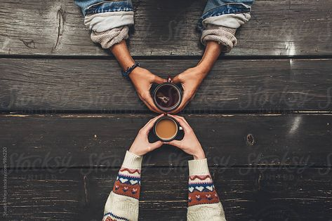 A view of a man and a woman holding cups of tea and coffee from above Download this high-resolution stock photo by STUDIO FIRMA from Stocksy United.