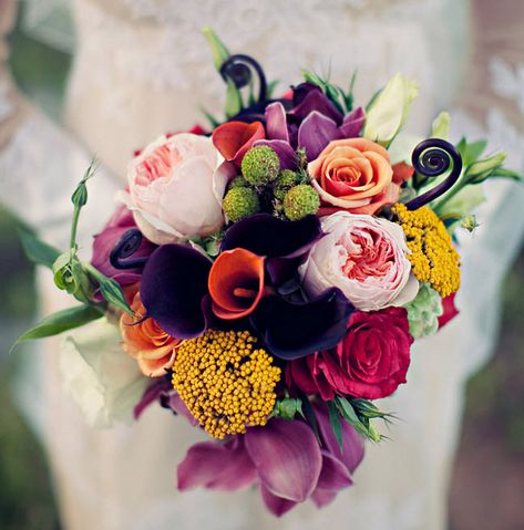 "The bride will carry a textured clutch bouquet of blush spray roses, orange ""Cherry Brandy"" roses, deep purple lisianthus with buds, green brunia baubles, brown fern curls, ""Roseberry"" roses, blush astilbe, and green geranium foliage wrapped in frayed ivory linen. The bridesmaids will carry smaller versions with no blush."