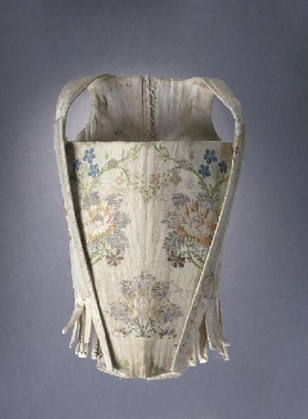 Corps à baleines ouvert avec un devant d'estomac amovible et réalisé dans deux étoffes différentes. Le devant est en taffetas écru façonné, broché de fils d'argent et de soie polychromes avec des motifs placés de grosses fleurs reliées entre elles par un rinceau végétal ; le derrière est en damas blanc à motifs de fleurs. Le corps est doublé d'une toile de coton ou de lin écrue. La forme de ce vêtement et les étoffes employées indiquent une datation vers 1750-1760