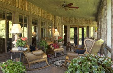 beautiful cozy porch; love the red pillow and splashes of color with the greenery....   Adirondack Style Boathouse