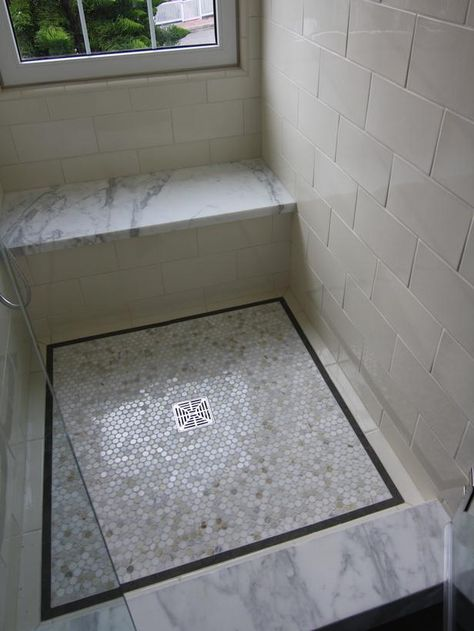 Marble slabs on the shower bench and curb coordinate with the penny tile floor in this elegantly detailed shower design. The shower is predominantly white, ensuring the area is a serene space for relaxation.