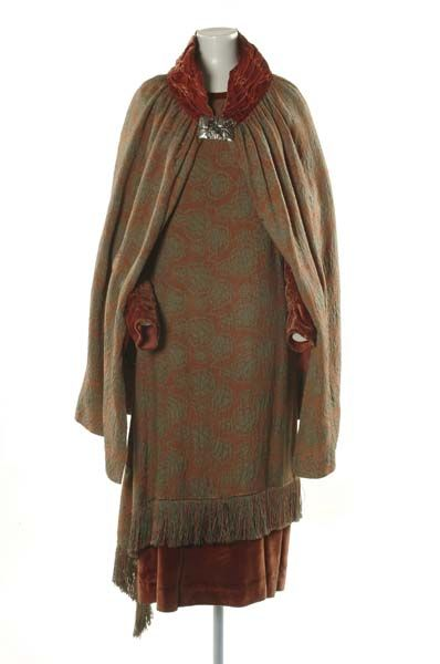 Ensemble, ca. 1912-18-- rose-red silk velvet underdress with long, ruched sleeves lined in rose-colored silk; rose & metallic silk brocade tabard with fringed edges; & brocade cloak with velvet collar & Art Nouveau buckle by Liberty.