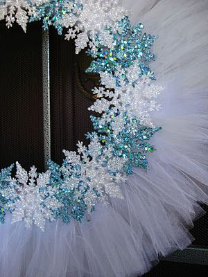 A little inexpensive white tulle and some Dollar Tree glittery snowflakes and... Voila!  Winter wreath!: