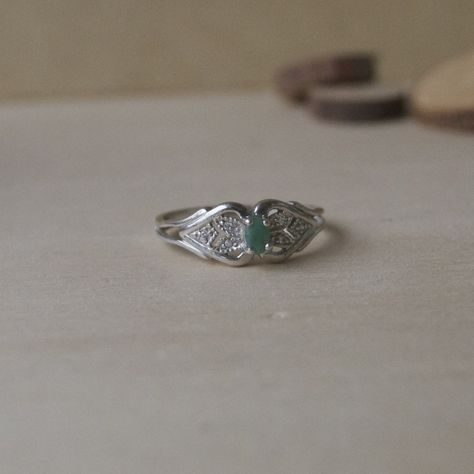 From wilderess.com: Vintage 1970's sterling silver ring with emerald colored stone and cubic zirconia filled heart detailing on either side of stone.