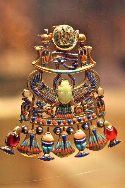 Tutankhamun pectoral with solar and lunar elements.  Cloisonné with carnelian, lapis lazuli, calcite, obsidian and coloured glass. At its centre is a chalcedony scarab, which has falcon legs and talons.