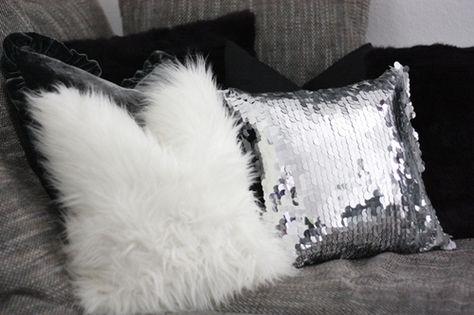 Black fur pillows, white fur pillows, silver sequined pillow.