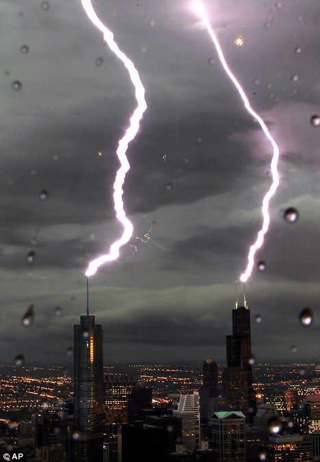 Bolt from the blue: Seen from the Hancock Tower, lighting strikes both the Willis Tower, right, and the Trump Tower in downtown Chicago as a severe storm rolls through the region.