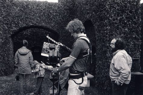 Preparing to film actors Shelley Duvall and Danny Lloyd on the daytime exterior Hedge Maze set of The Shining at MGM Esltree Studios. Director Stanley Kubrick watches as a slate is held in front of Steadicam operator Garrett Brown.