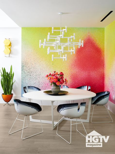 Neon wallpaper decorated with a spray paint pattern makes this dining room pop. Modern dining chairs and a midcentury style dining table add flair. See more on HGTV.com.
