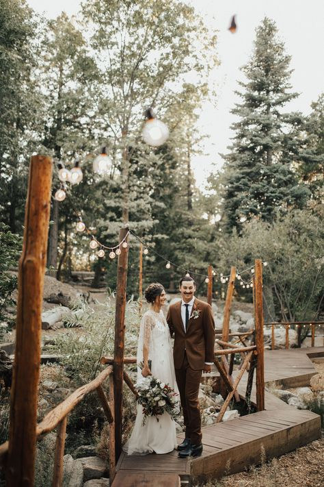 Kick up the magic of your woodland wedding by stringing bistro lights throughout the reception area. Whether you string them among the trees or along with structures at your venue, they'll be sure to cast your reception in an ethereal glow. Click through for more forest wedding ideas! #forestwedding #forestweddingideas #forestweddings #bohowedding #bistrolights #weddingreceptiondecor
