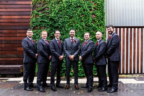 Stylish groomsmen with ivy wall at The Joinery Chicago wedding venue
