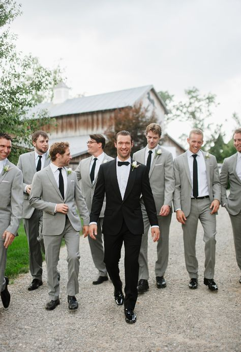The groom looks dapper in his black tux and bow tie with the groomsmen in light gray suits with black ties ~ we ❤ this! moncheribridals.com