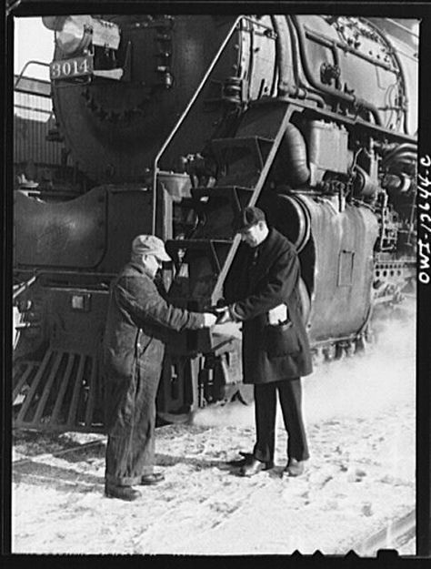 Chicago, Illinois. Conductor handling engineer copy of train orders before a Chicago and Northwestern Railroad freight train pulls out for Clinton, Iowa. Since the track between those points is under automatic train control, the engineer, in turn, hands the conductor the key to the automatic train control lock of the engine. The conductor will keep the key in the caboose until the train arrives at its destination.  Photo taken by Jack Delano, January 1943.