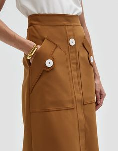 Ritzy Fence Patch Pocket A-Line Skirt NOTE: UK SIZES LISTED. See sizing guide for conversion information. Commanding skirt from Ellery in Camel. Concealed back zip-and-button cl.