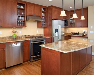 Exceptionnel Custom Cherry Cabinets From Baywood Cabinets Provide A Colorful  Counterpoint To The Oak Flooring. A Dedicated Kitchen Desk Area Keeps  Everyone In The Family ...
