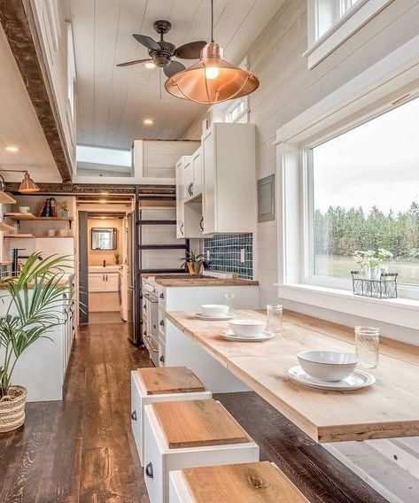 The clients wanted space for family dinners and floor space for the kids to play, so Summit Tiny Homes built a long oak table that folds down when not in use. The table also folds in three parts if they don't want the whole table up at once.
