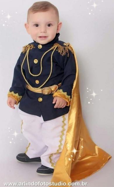 817d09a72f01 Menino vestido de príncipe, comc calça branca, blusa azul marinho e capa  dourada.
