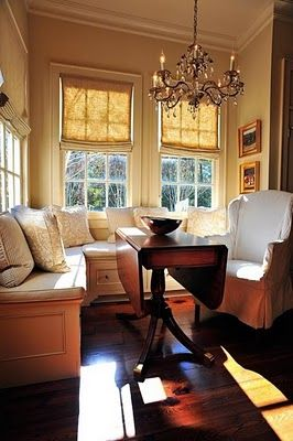 Cozy breakfast nook with window seats, drop leaf antique tabe, a slip covered wing chair and chandelier