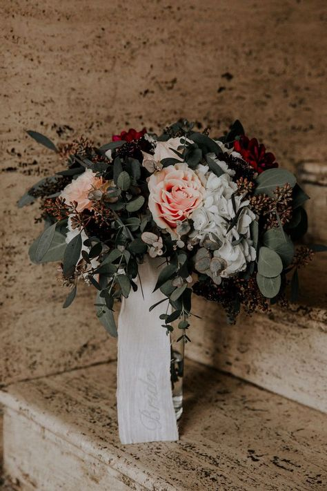 The rich burgundy, blush pink and eucalyptus give this bridal bouquet a sumptuous look. #weddingflorals #weddingplanning #weddingcolors