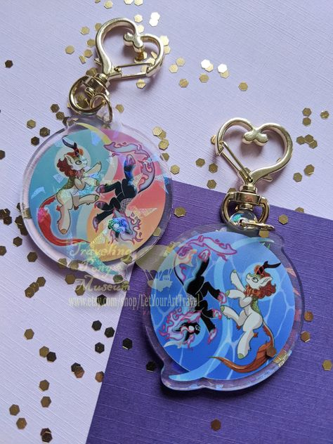 """""""This is a 2\"""" acrylic keychain featuring artwork of Fall Kirin Myth from Your Small Horses by Inky Notebook. This charm has a holographic accent! All charms are double sided print with clear acrylic. All of our charms come with a durable clip closure - heart or star style in bright gold - so they will never come loose on your travels. They are also scratch resistant and water proof for all your daring adventures. All charms are professionally designed and printed by the Traveling Pony Museum us"""