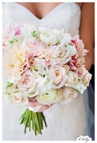 a bridal bouquet a clutch bouquet of cream hydrangeas ivory garden roses blush pink dahlias blush pink spray roses white freesia gold seeded