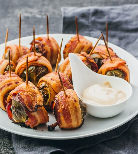 Roasted bacon wrapped brussels sprouts on a white plate served with a balsamic mayo dip #thanksgiving #food #recipes #thanksgivingrecipes #appetizers #thanskgivingappetizers