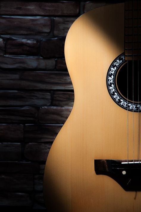 A Beam Of Light Falls On An Acoustic Guitar Standing On The Background Of A Brick Wall.