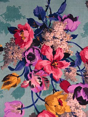 Floral This Printed Velveteen Remnant, depicts saturated magenta, purple, and aqua with splashes of ochre.