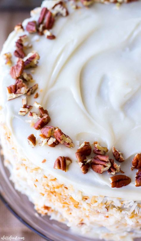 This easy Carrot Cake recipe is made with carrot puree and oil, which makes it so moist! This carrot spice cake without raisins is filled with coconut and topped with cream cheese frosting. The best Easter cake! #cake #recipe #dessert #carrotcake #creamcheese