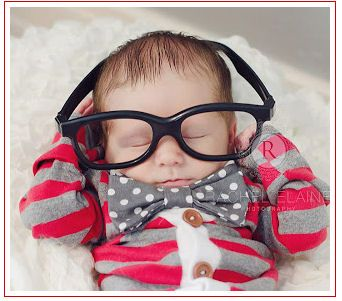 Sweet newborn baby portrait of a baby boy wearing dad's glasses and a polka dot bow tie.