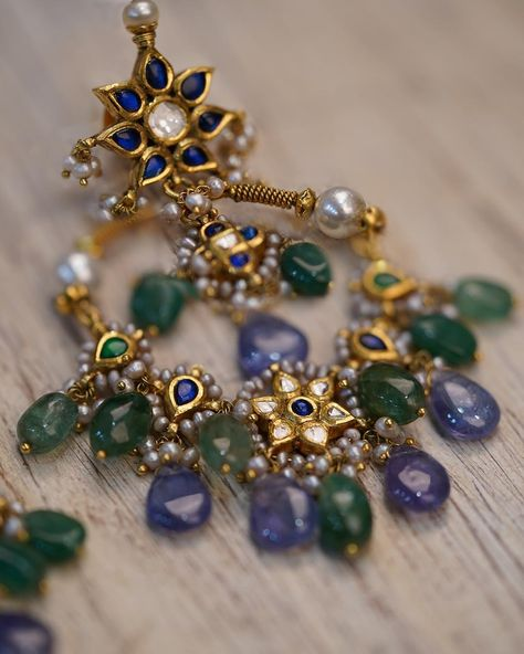 An Indian version of the trendy 'hoop' earrings, the Laguna baalis are inspired by the colors of the sea. They can add a contemporary touch to a traditional, and even a vintage Indian outfit. The earrings are designed in gold with uncut diamond and finished with beads of tanzanite and emerald gemstones. Estimated Details : Gold(18K) : 21.46 gm Gold(22K) : 5.95 gm Tanzanite : 58 ct Emeralds : 36 ct (The above weights are indicative)Note: If the design is not readily available it will be made to o
