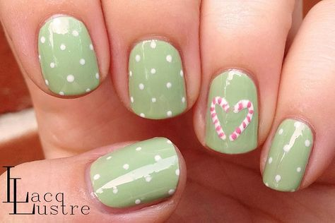 Simple yet pretty Christmas nail art. Design your nails in green polish topped with white polka dot polishes and candy cane details.