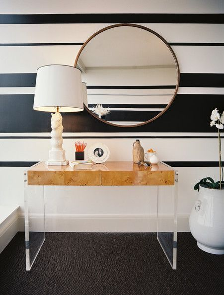Striped walls behind a round mirror and a wooden desk.