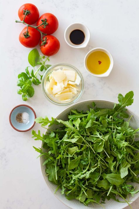 A super simple yet incredibly delicious Arugula Salad. Arugula, tomatoes, and Parmesan cheese are the perfect combination for a salad. It will steal the show without taking much time to prepare. #summersalad #vegetarian #arugulasalad #easysalad