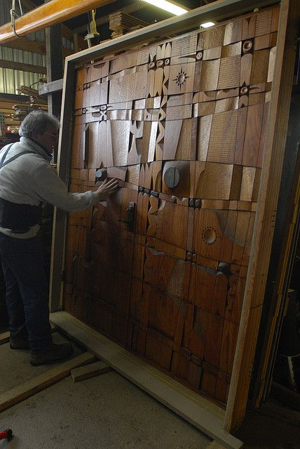Carved teak doors by acclaimed sculptor, the late LeRoy Setziol, recently reclaimed at a demo site by McGee Salvage, purveyors of fine reclaimed woods and floors.