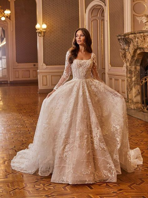 A gown unlike any other, Val Stefani Style Floria is beautiful as can be. This long sleeve wedding dress features ornate embroidered lace appliques with equine, crystals, pearls and glass beading details that will have you feeling confident as can be. The ball gown skirt features a bouquet shimmer net detailing, leaving you look flawless as can be. #weddingdressideas #weddinggowns #bridalballgowns #longsleeveweddingdresses