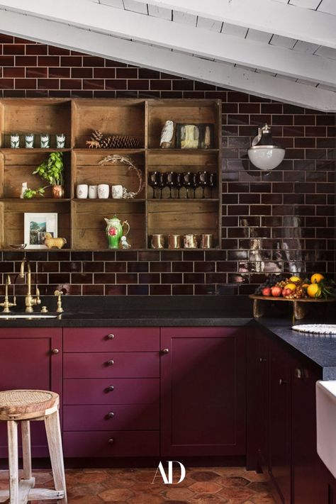 The actor and her designer opted for a darker, moodier kitchen rather than an all-white space. Aubergine wall tile by Waterworks, 19th-century terra-cotta floor tiles by Chateau Domingue, majolica backsplash and marble by Compas Stone, a cubby shelf from Nickey Kehoe, and a Pierre Jeanneret stool from Galerie Half all fill the cozy cooking space. #beams #subwaytiles #barstools #barstool #countertop #sink #beams #openshelving #cozy #kitchen #cooking #ranchhouse #ranchhome #faucet #vases #lighting
