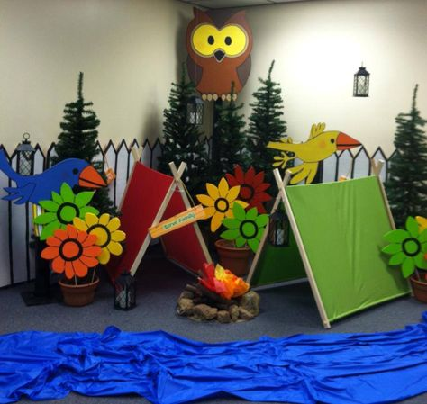 """""""God's Backyard Bible Camp"""" campground with tents made from Pinterest along with foam owl, birds, picket fence and flowers along with a campfire with red, orange and yellow tissue for fire. Five Christmas trees were bought on sale last Christmas to finish out the scene."""