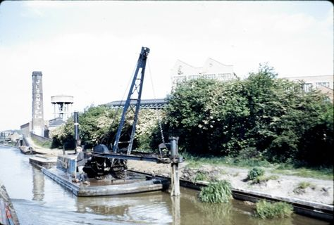 """Caption: """"GU Paddington Arm"""" BW197/2/26/43  Image showing piling work being carried out near Southall in the 1960's, and the towpath bridge over wharf entrance to J. Lyons. #London #canal #Boat"""
